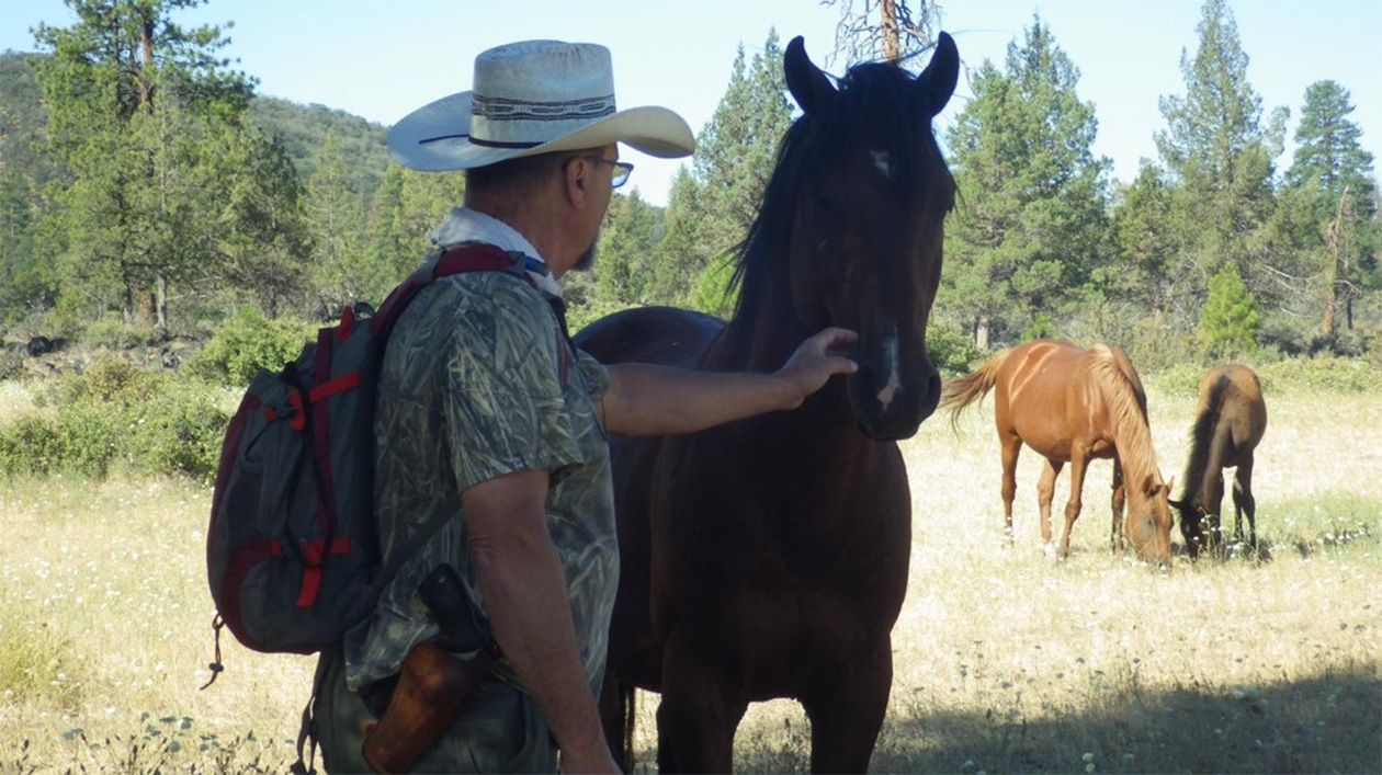 William E. Simpson II – Naturalist is greeted by a mighty wild mountain stallion in the wilderness.